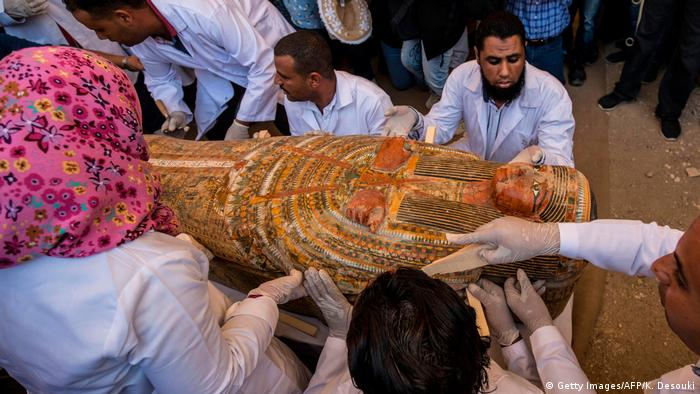 Egyptian archaeologists open a wooden coffin belonging to a woman (Getty Images/AFP/K. Desouki)