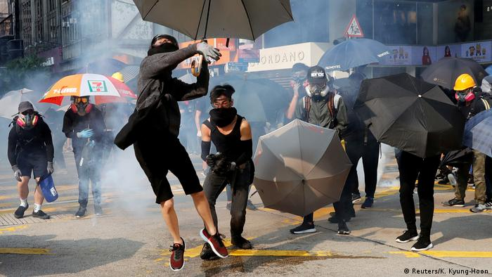 A demonstrator holding an umbrella throws a tear gas canister back at police
