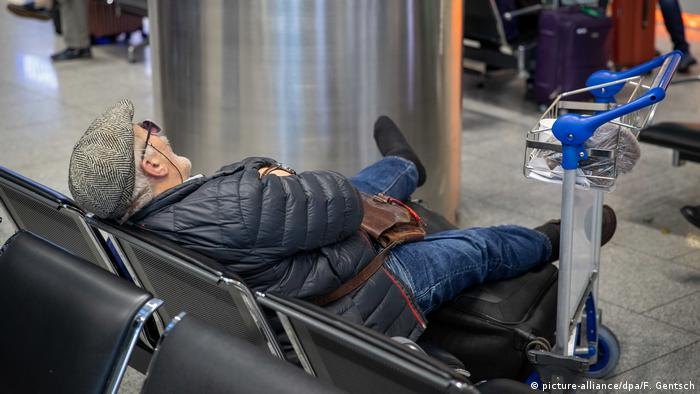A man sleeps, waiting for his delayed flight in Dusseldorf