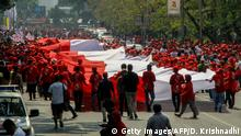Supporters of Indonesia's President Joko Widodo wave a giant Indonesian flag in Jakarta on October 20, 2019, ahead of Widodo's inauguration for a second term. - Widodo was to kick off a fresh term on October 20, facing a wave of crises and with Jakarta under heavy security days after Islamist militants tried to assassinate his top security minister. (Photo by DANY KRISNADHI / AFP) (Photo by DANY KRISNADHI/AFP via Getty Images)