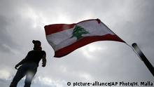 An anti-government protester stands next to a Lebanese flag on the rooftop of the Opera building, as he watches other protesters, in downtown Beirut, Lebanon, Sunday, Oct. 20, 2019. Lebanon is bracing for what many expect to be the largest protests in the fourth day of anti-government demonstrations. Thousands of people of all ages were gathering in Beirut's central square Sunday waving Lebanese flags and chanting the people want to bring down the regime. (AP Photo/Hussein Malla) |
