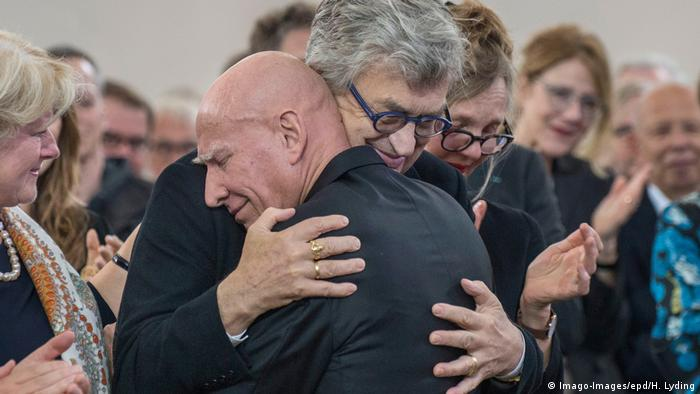 Sebastiao Salgado and director Wim Wenders embrace while a crowd of people clap behind them