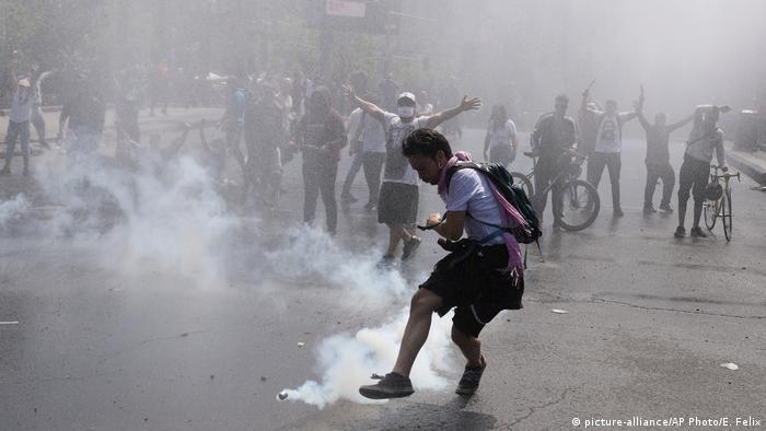 A protester kicks a tear gas canister