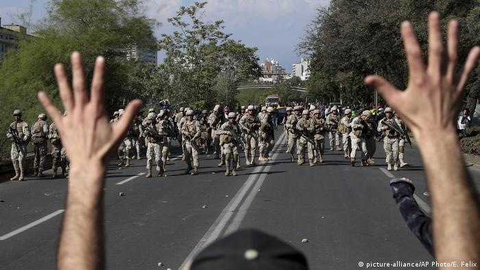 Protester in Chile raises his hands in front of a line of soldiers