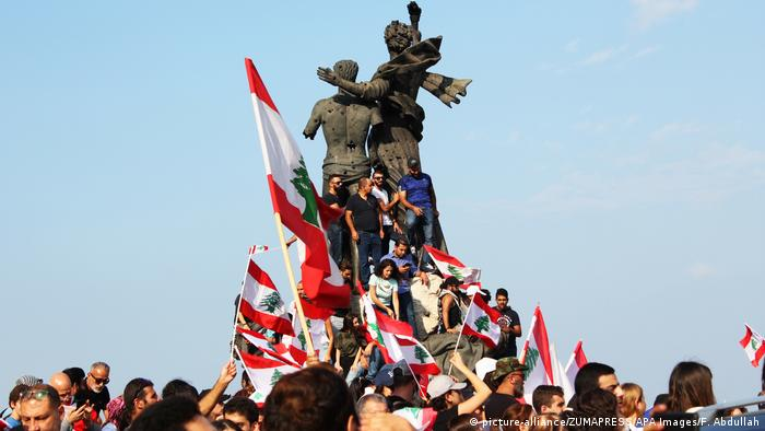 Protesters stand around a statue waving Lebanese flags