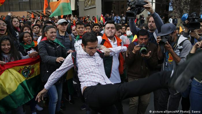 Supporters of opposition presidential candidate Carlos Mesa, a former president, hold back a fellow supporter trying to kick supporters of Bolivian President Evo Morales