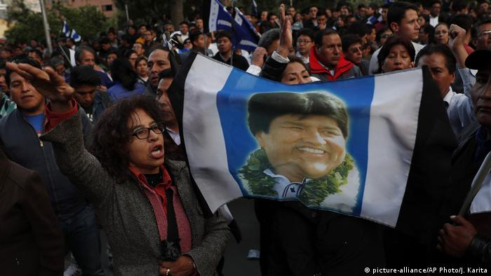 Supporters in Bolivia hold a photo of Evo Morales