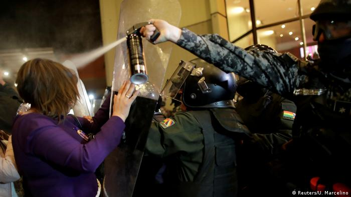 A riot police officer releases pepper spray on demonstrators during a protest in La Paz, Bolivia