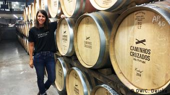 WinemakerLígia Santos stands in front of wine casks at her family's vineyard in Portugal
