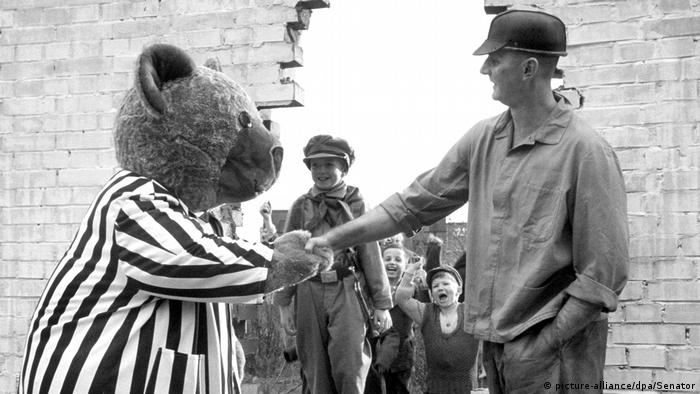 Escena de Helden wie wir, de Sebastian Peterson: un hombre le da la mano a un oso ante el Muro de Berlín, que ya cayó.