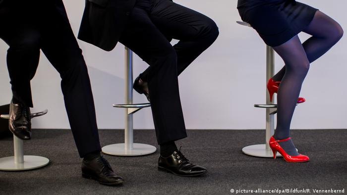 Executives sit crosslegged on stools