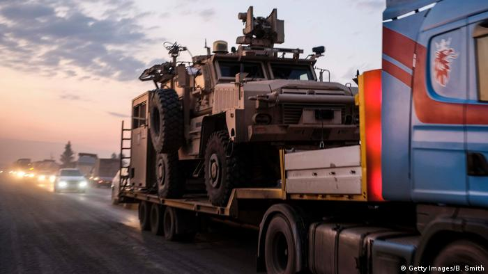 A convoy of U.S. armored military vehicles leave Syria on a road to Iraq