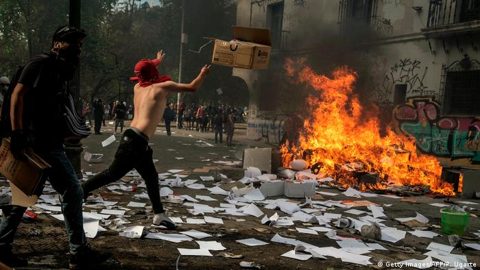 A man wearing a red scarf on his head throws a cardboard box onto a fire in the street