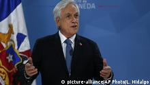 """Chilean President Sebastián Piñera addresses the nation from La Moneda presidential palace, amid ongoing demonstrations triggered by an increase in subway fares in Santiago, Chile, Monday, Oct. 21, 2019. Protesters defied an emergency decree and confronted police in Chile's capital Monday, continuing violent clashes, arson and looting that have left at least 11 dead and led the president to say the country is """"at war."""" (AP Photo/Luis Hidalgo) 