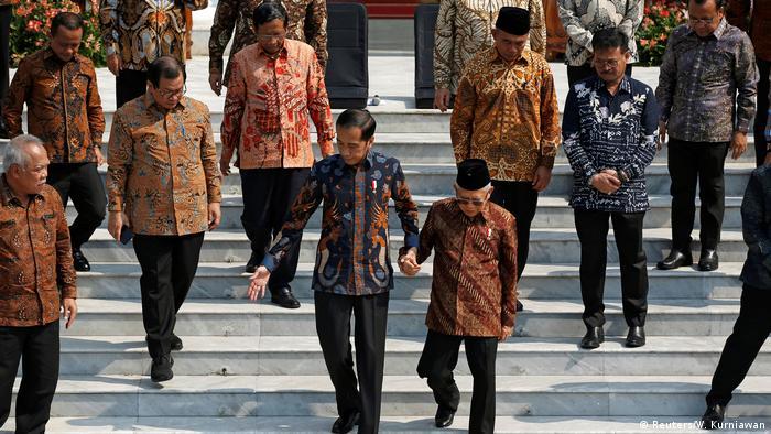 Presiden Joko Widodo menuntun Wakil Presiden Ma'ruf Amin di Istana Merdeka