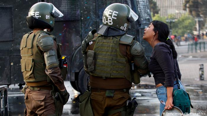 Una joven mujer habla con militares en las calles de Santiago de Chile. (22.10.2019).