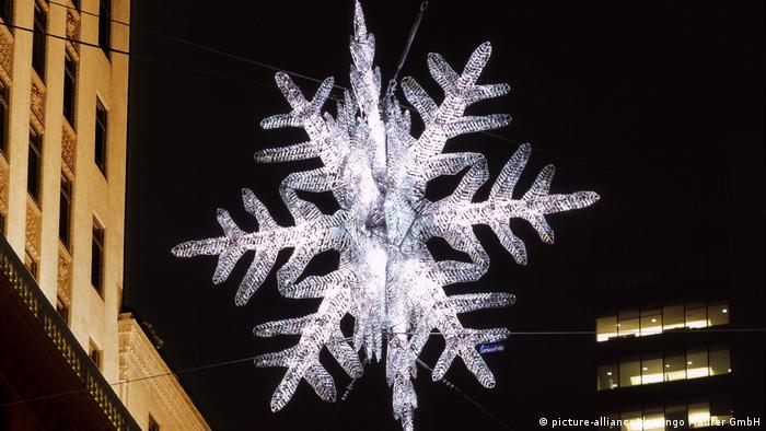 A crystal snowflake enlightens a street in front of a high-rise building (Foto: picture-alliance/dpa/Ingo Maurer GmbH).