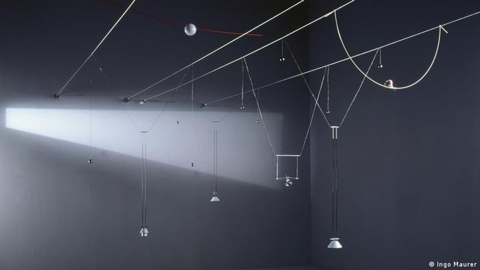 A dark room is lightened by halogen lamps hanging on horizontal wires (Photo: Ingo Maurer).