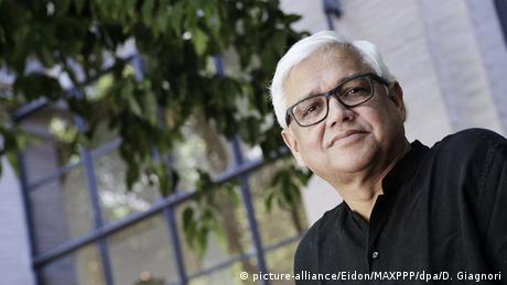 Der Schriftsteller Amitav Ghosh trägt ein schwarzes Hemd und eine Brille mit schwarzem Gestell. Er schaut in die Kamera.