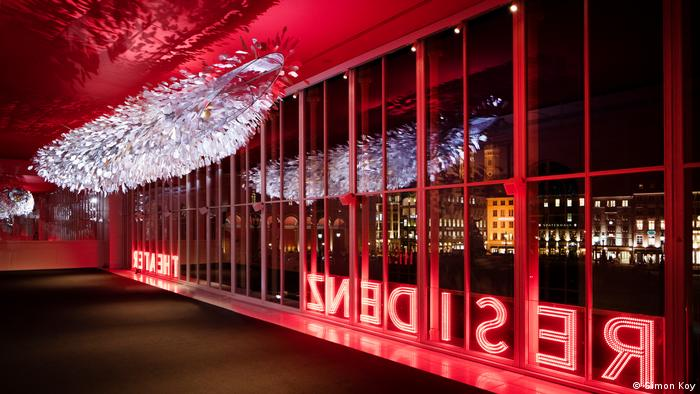 An empty foyer enlightened in red with a huge glass wall and a 12 meter long silver-colored light installation (Foto: Simon Koy).