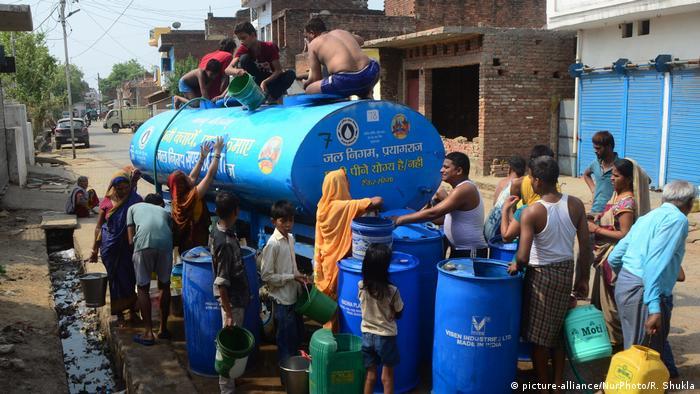 Blauer Wassercontainer und Menschenmengen