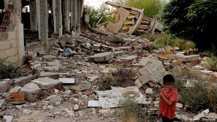 A child standing in front of a destroyed church in the village of Tell Tamer in northwestern Syria