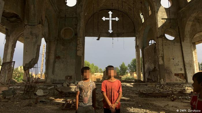 Two boys stand in a destroyed church