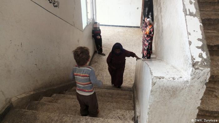 Ребенок стоит на верху лестницы, женщина поднимается к нему