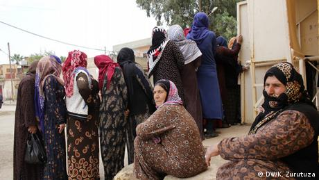 A group of women queuing for bread