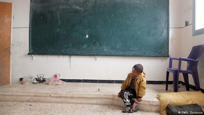 Un niño en una sala de clases convertida en refugio.