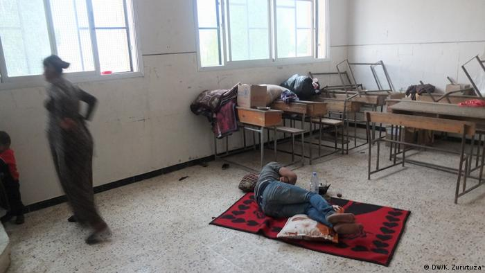 A man lying on a rug in an abandoned school