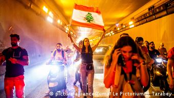 Lebanese protesters carry a national flag while they walk through a tunnel (picture-alliance/Zuma/ Le Pictorium/B. Tarabey)