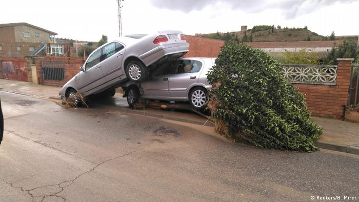 A car is swept on top of a tree and another car in Spain