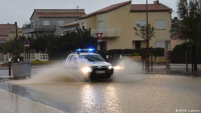 A police car drives through flood waters in France