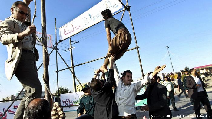 Men hold a man hanged in public, to prevent his execution.