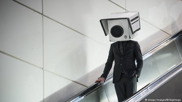 Человек с коробкой в виде скрытой камеры на голове в знак протеста против технологии распознавания лиц