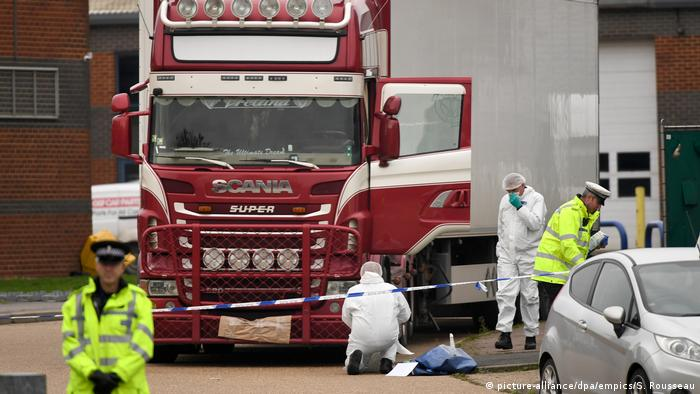 Forensic workers examine the truck in which 39 people were found dead