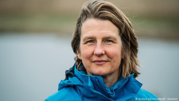 A portrait of Silke Backsen in a blue rain jacket