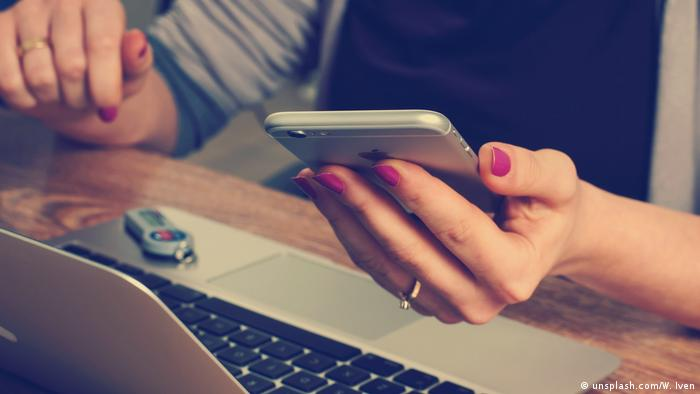 Aclose upof a woman's hand holding a smartphone while she uses a laptop