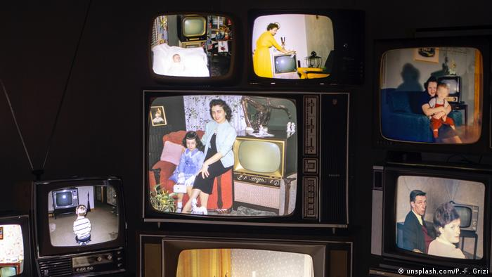 Old televisions switched on and showing various images