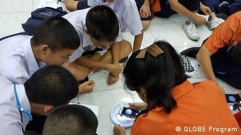 Estudiantes tailandeses trabajan en un proyecto para identificar larvas de mosquitos.