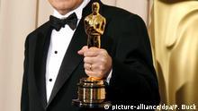 epa00942419 Director Ennio Morricone holds up his Honorary Award Oscar at the 79th Annual Academy Awards at the Kodak Theatre in Hollywood, California Sunday 25 February 2007. EPA/PAUL BUCK |