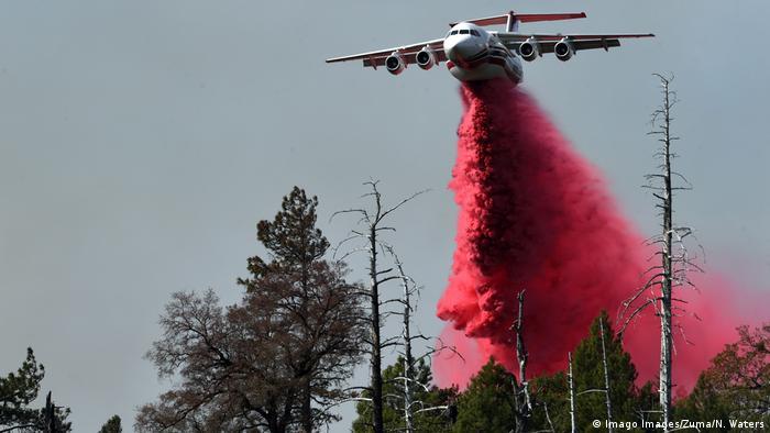A plane drops fire retardant onto a blaze in northern California