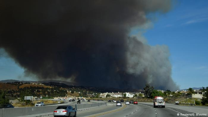 A plume of smoke rises above a highway in California