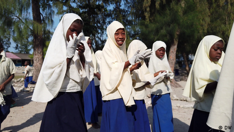 DW Eco Africa - School pupils in Zanzibar wearing a uniform of a dark blue dress and white headscarf. They are putting on gloves in preparation for collecting letter.