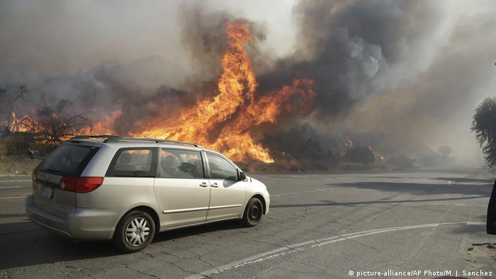 A car drives by a wildfire in southern California