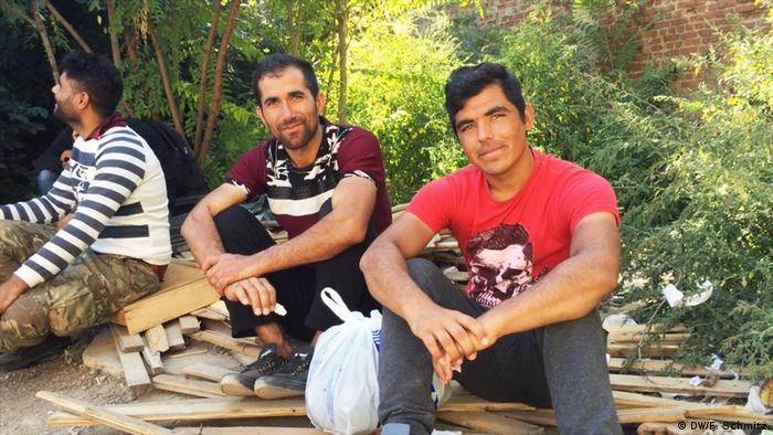 Three male refugees sitting on a pile of building timber in Thessaloniki