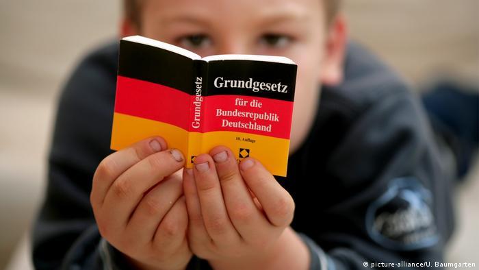 Child reads German Basic Law