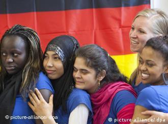 Junge Frauen aus verschiedenen Ländern vor einer Deutschland-Fahne (Foto: dpa)