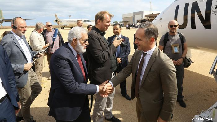 Libya's Foreign Minister Mohamed Taher Siala welcomes his German counterpart Heiko Maas upon his arrival at Zuwarah International Airport, about 160 km west of Tripoli, on October 27, 2019